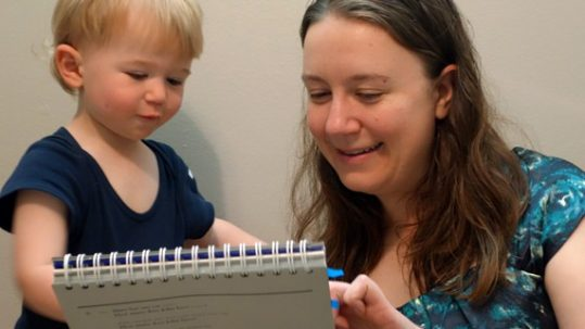 Dr. Sara Kover in the lab with a young study participant.