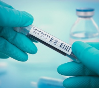 gloved hands holding a vial labeled coronavirus