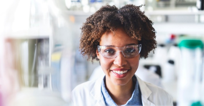 a scientist smiling in a lab