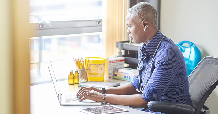 A female doctor sits at her desk