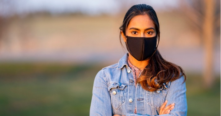 hispanic woman in a black face mask and a denim jacket looking at the camera