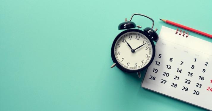 an alarm clock, a wall calendar and a pencil